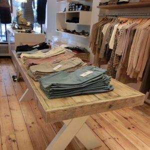 Houten handgemaakte tafel met witte houten X-poten voor kledingwinkel | stoerhout-hetgooi.nl